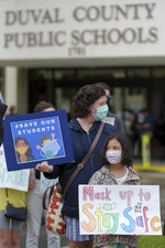 Lori Eisenberg-Castro and her daughter, Eyla, 8, participate in a pro-mask rally outside the school board building Tuesday, Aug. 3, 2021, in Jacksonville, Fla. Around 50 people gathered outside the Duval County School Board building in support of having mandatory masking of teachers and students ahead of the school board taking up the issue in their Tuesday evening meeting. Florida's Gov. Ron DeSantis has forbidden mandating masks in Florida's public schools despite CDC recommendations to wear masks due to the recent surge of COVID-19 infections which are particularly high in Northeast Florida. (Bob Self/The Florida Times-Union via AP)