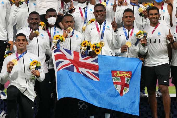 Member's of Fiji's team and staff hold a national flag, as they pose with their gold medals in men's rugby sevens at the 2020 Summer Olympics, Wednesday, July 28, 2021 in Tokyo, Japan. (AP Photo/Shuji Kajiyama)