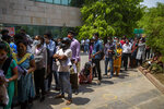 People wait for their turn to be tested for COVID-19 at a government hospital in Noida, a suburb of New Delhi, India, Thursday, April 15, 2021. India reported more than 200,000 new coronavirus cases Thursday, skyrocketing past 14 million overall as an intensifying outbreak puts a grim weight on its fragile health care system. (AP Photo/Altaf Qadri)