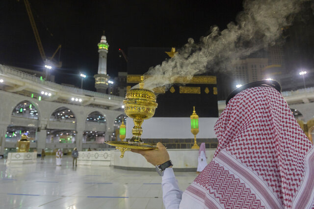 A man burns incense as the area around the Kaaba, the square structure in the Great Mosque, toward which believers turn when praying, is prepared for pilgrims, in Mecca, Saudi Arabia, late Sunday, July 26, 2020. Anywhere from 1,000 to 10,000 pilgrims will be allowed to perform the annual hajj pilgrimage this year due to the virus pandemic. (Saudi Ministry of Media via AP)