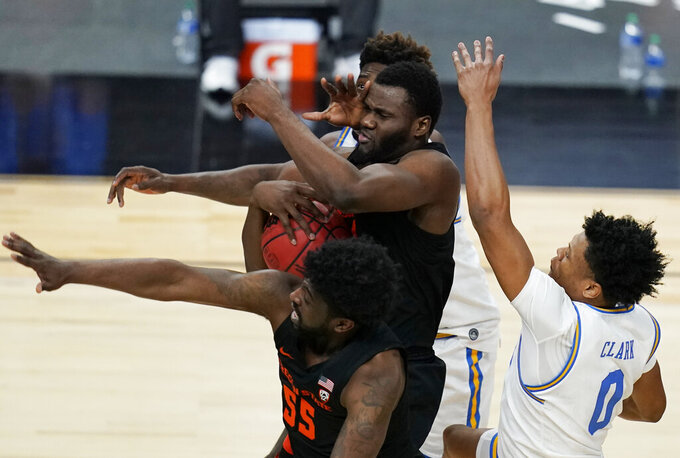Oregon State's Rodrigue Andela (34) grabs a rebound over UCLA during overtime of an NCAA college basketball game in the quarterfinal round of the Pac-12 men's tournament Thursday, March 11, 2021, in Las Vegas. (AP Photo/John Locher)