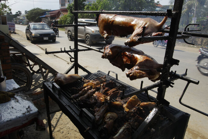 FILE - In this Mar. 30, 2017, file photo, a local vendor grills dog meat on the sidewalk on the outskirts of Phnom Penh, Cambodia. Early this week on Monday, July 6, 2020 in Siem Reap, home of the famous Angkor Wat temple complex, the local government issued a ban on the buying, selling and butchering of dogs for food. (AP Photo/Heng Sinith, File)