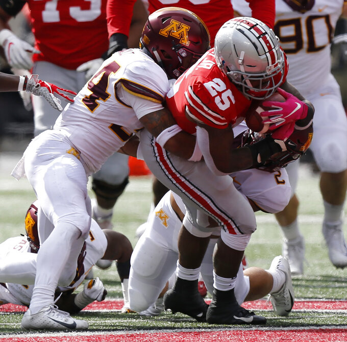 Ohio State running back Mike Weber (25) is tackled by Minnesota defensive backs Antonio Shenault, left, and Jacob Huff during the first half of an NCAA college football game Saturday, Oct. 13, 2018, in Columbus, Ohio. (AP Photo/Jay LaPrete)