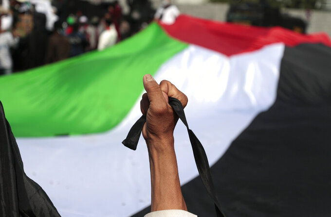 A Muslim man raises his fist in front of a large Palestinian flag during a rally against Israel's attacks on Gaza, outside the U.S. Embassy in Jakarta, Indonesia, Friday, May 21, 2021. (AP Photo/Dita Alangkara)