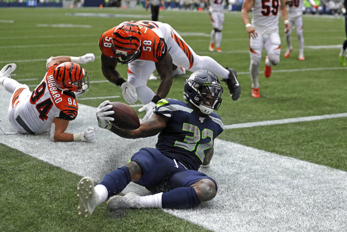 Seattle Seahawks running back Chris Carson (32) scores a touchdown against the Cincinnati Bengals during the first half of an NFL football game, Sunday, Sept. 8, 2019, in Seattle. (AP Photo/Stephen Brashear)