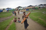 FILE - In this June 24, 2014, file photo, a Rohingya boy walks with a mat as children play in the background at Dar Paing camp for Muslim refugees in north of Sittwe, western Rakhine State, Myanmar. The de facto detention of 130,000 ethnic Rohingya in squalid camps in Myanmar amounts to a form of apartheid, a human rights group alleged Thursday, Oct. 8, 2020 in urging the world to pressure Aung San Suu Kyi's government to free them. (AP Photo/Gemunu Amarasinghe, File)
