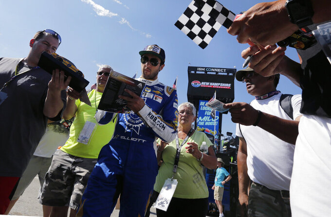 Chase Elliott signs autographs for fans as he heads to his garage during a NASCAR Cup Series auto race practice at New Hampshire Motor Speedway in Loudon, N.H., Saturday, July 20, 2019. (AP Photo/Charles Krupa)