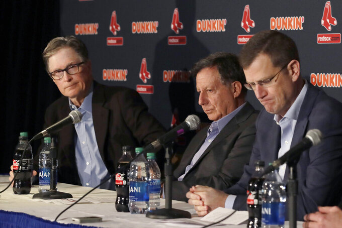 FILE - From left, in a Jan. 15, 2020, file photo, Boston Red Sox owner John Henry, chairman Tom Werner and CEO Sam Kennedy react during a news conference at Fenway Park in Boston. The Boston Red Sox were stripped of their second-round pick in this year's amateur draft by Major League Baseball for breaking video rules in 2018 and former manager Alex Cora was suspended through the 2020 postseason for his conduct as bench coach with the Houston Astros the previous year. Baseball Commissioner Rob Manfred announced his decision Wednesday, April 22, 2020, concluding Red Sox replay system operator J.T. Watkins used in-game video to revise sign sequences provided to players. (AP Photo/Elise Amendola, File)