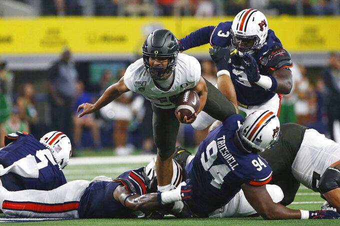 Oregon running back Travis Dye (26) runs for a short gain as Auburn defensive end Marlon Davidson (3) closes in during the first half of an NCAA college football game, Saturday, Aug. 31, 2019, in Arlington, Texas. (AP Photo/Ron Jenkins)