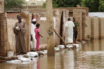 People walk on sandbags to reach their homes in the town of Shaqilab, about 15 miles (25 km) southwest of the capital, Khartoum, Sudan, Monday, Aug. 31, 2020. (AP Photo/Marwan Ali)