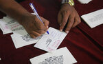 FILE- In this Jan. 24, 2017 file photo, a Sri Lankan media rights activist signs a postcard addressed to president Maithripala Sirisena during a petition signing demanding that Sirisena appoint a presidential commission to investigate all abductions during the country's brutal, decades-long civil war, in Colombo, Sri Lanka.  Forced to flee their country a decade ago to escape allegedly state-sponsored killer squads, Sri Lankan journalists living in exile doubt they'll be able to return home soon or see justice served to their tormentors _ whose alleged ringleader could come to power in this weekend's presidential election. Exiled journalists and media rights groups are expressing disappointment over the current government's failure in punishing the culprits responsible for crimes committed against media members. (AP Photo/Eranga Jayawardena, File)