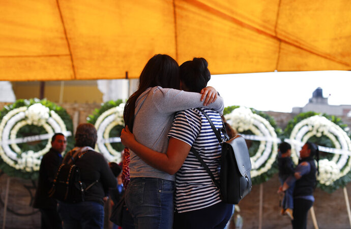 Relatives of the students and faculty who were killed when a building collapsed at the Enrique Rebsamen school during the 2017 earthquake embrace following a Catholic Mass next to the remains of the school, in southern Mexico City, Thursday, Sept. 19, 2019. Mexico was marking Thursday the Sept. 19 anniversaries of the 2017 earthquake that killed more than 300 people and a devastating 1985 temblor that left at least 9,500 dead.(AP Photo/Rebecca Blackwell)