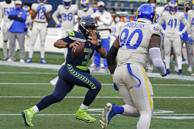 Seattle Seahawks quarterback Russell Wilson (3) runs for a touchdown as Los Angeles Rams defensive lineman Michael Brockers (90) looks on during the second half of an NFL football game, Sunday, Dec. 27, 2020, in Seattle. (AP Photo/Elaine Thompson)