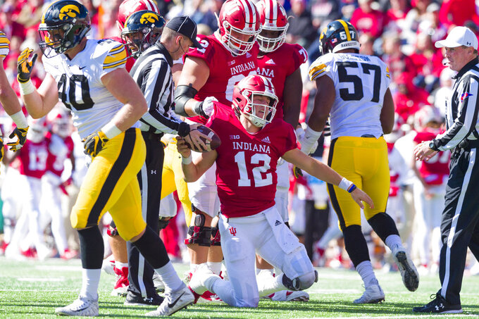Indiana quarterback Peyton Ramsey (12) is helped to his feet by his teammates after being sacked by the Iowa defense during the first half of an NCAA college football game Saturday, Oct. 13, 2018, in Bloomington, Ind. (AP Photo/Doug McSchooler)