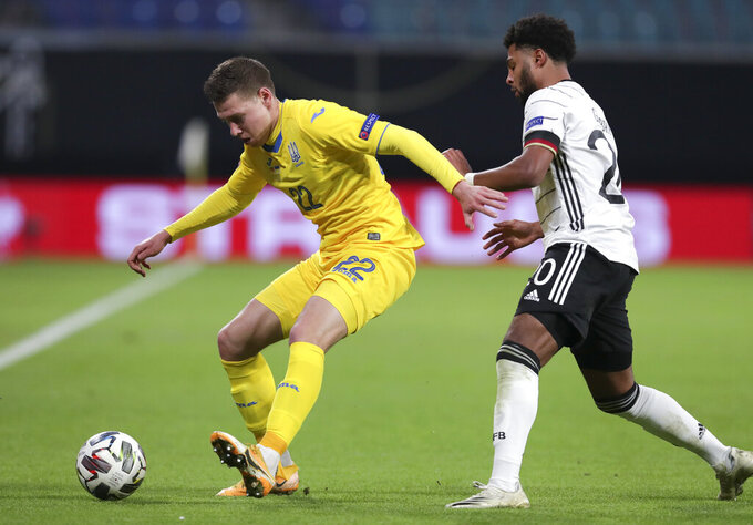 Ukraine's Mykola Matwijenko, left, and Germany's Serge Gnabry battle for the ball during the UEFA Nations League soccer match between Germany and the Ukraine at the Red Bull Arena in Leipzig, Germany, Saturday, Nov. 14, 2020. (AP Photo/Michael Sohn)