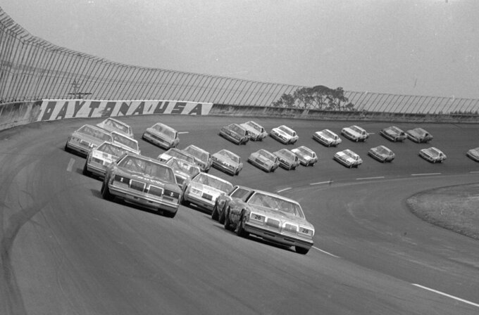 FILE - In this Feb. 18, 1979, file photo, 41 cars roll around the wet Daytona International Speedway track under a caution flag as the Daytona 500 auto race gets under way in Daytona Beach, Fla. The 1979 race was instrumental in broadening NASCAR's southern roots. Forty years later, it still resonates as one of the most important days in NASCAR history. (AP Photo, File)