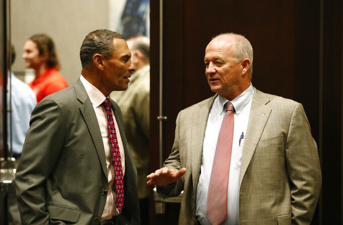 Fresno State head coach Jeff Tedford, right, and Arizona State head coach Herm Edwards speak with each other before a news conference for the Las Vegas Bowl, Friday, Dec. 14, 2018, in Las Vegas. (AP Photo/John Locher)