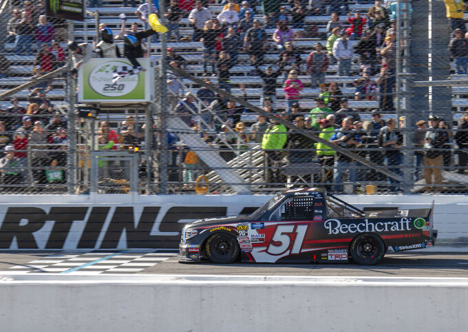 Kyle Busch takes the checkered flag under caution during the NASCAR Gander Outdoors Truck Series race at Martinsville Speedway in Martinsville, Va. Saturday, March 23, 2019. (AP Photo/Matt Bell)
