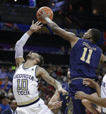 Notre Dame's Juwan Durham (11) blocks a shot by Georgia Tech's Jose Alvarado (10) during the first half of an NCAA college basketball game in the Atlantic Coast Conference tournament in Charlotte, N.C., Tuesday, March 12, 2019. (AP Photo/Nell Redmond)