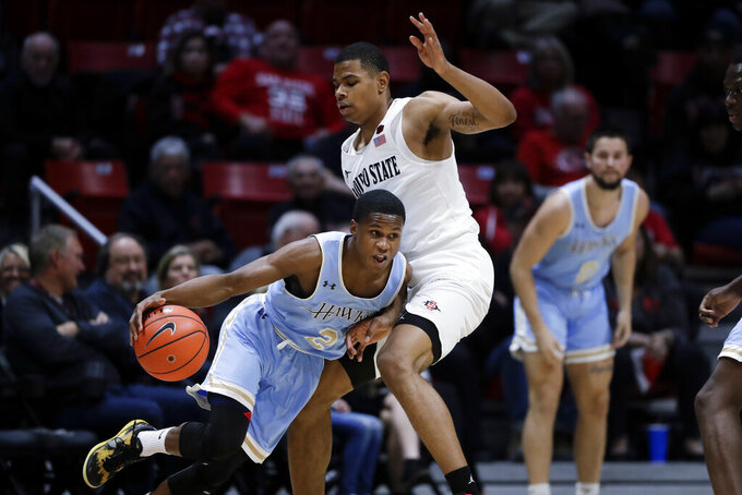 San Diego Christian guard Teyden Gause, left, drives as San Diego State forward Keshad Johnson defends during the first half of an NCAA college basketball game Wednesday, Dec. 18, 2019, in San Diego. (AP Photo/Gregory Bull)