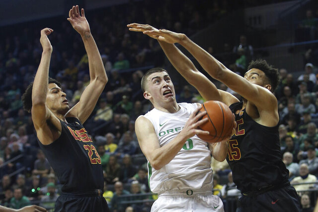 Oregon's Payton Pritchard, center, goes up for a shot between Southern California's Max Agbonkpolo, left, and Isaiah Mobley, right, during the first half of an NCAA basketball game in Eugene, Ore., Thursday, Jan. 23, 2020. (AP Photo/Chris Pietsch)