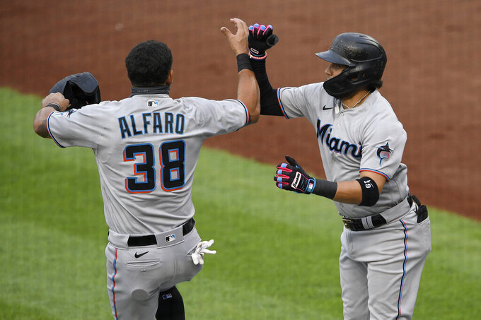 Miami Marlins' Miguel Rojas, right, celebrates his three-run home run with Jorge Alfaro (38) during the second inning of a baseball game against the Washington Nationals, Friday, Aug. 21, 2020, in Washington. (AP Photo/Nick Wass)