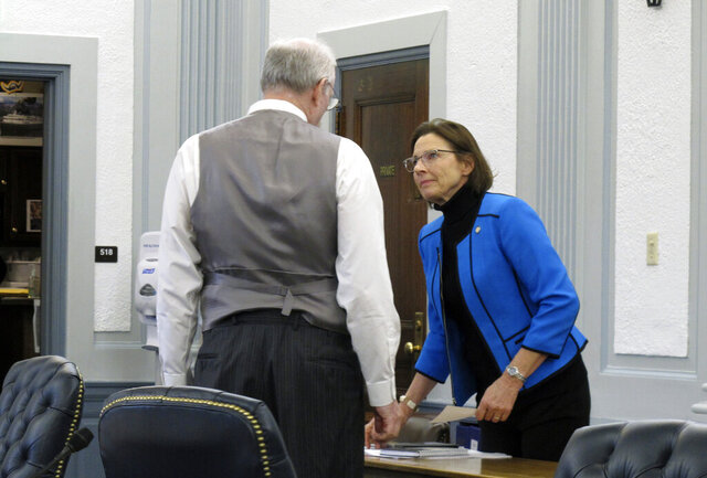 Alaska Senate President Cathy Giessel, right, speaks to Senate Finance Committee Co-chair Bert Stedman before the start of a budget conference committee meeting on Friday, March 27, 2020, in Juneau, Alaska. A conference committee of House and Senate negotiators was tasked with hammering out differences on a state spending package. (AP Photo/Becky Bohrer)
