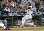 Minnesota Twins' Jorge Polanco (11) begins his slide home to score as Seattle Mariners catcher Tom Murphy readies a tag during the fifth inning of a baseball game Friday, May 17, 2019, in Seattle. (AP Photo/Elaine Thompson)