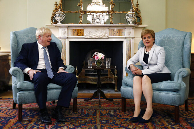 """FILE - In this Monday. July 29, 2019 file photo, Scotland's First Minister Nicola Sturgeon, right, sits with Britain's Prime Minister Boris Johnson, in Bute House, ahead of their meeting, in Edinburgh, Scotland.   Johnson has inflamed Scottish discontent with his Conservative government by reportedly saying that giving governing powers to Scotland had been a """"disaster."""" British media reported that Johnson made the remarks during a video meeting with Conservative Party lawmakers on Monday, Nov. 16, 2020, in which he also said Scottish devolution had been former Prime Minister Tony Blair's """"biggest mistake."""" (Duncan McGlynn/Poo Photo via AP, File )"""