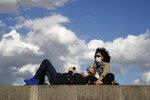 Parisians, wearing protective masks, sit in the sun along the closed Tuileries garden in Paris, Saturday, May 23, 2020 as France gradually lifts its COVID-19 lockdown. (AP Photo/Francois Mori)