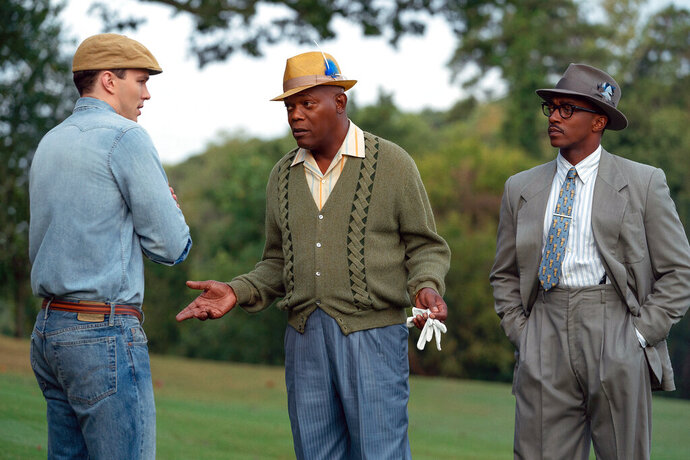 """This image released by Apple TV Plus shows, from left, Nicholas Hoult, Samuel L. Jackson and Anthony Mackie in a scene from """"The Banker."""
