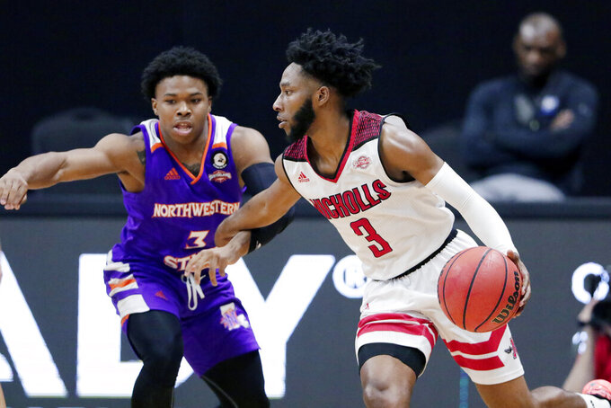 Nicholls State guard Kevin Johnson, right, looks to drive around Northwestern State guard Brian White, left, during the second half of an NCAA college basketball game in the Southland Conference semifinals Friday, March 12, 2021, in Katy, Texas. (AP Photo/Michael Wyke)