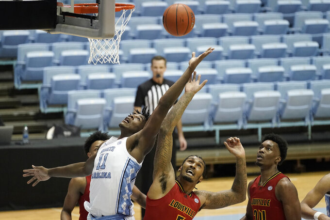 North Carolina forward Day'Ron Sharpe (11) drives to the basket against Louisville center Malik Williams while Louisville forward Jae'Lyn Withers (24) watches during the first half of an NCAA college basketball game in Chapel Hill, N.C., Saturday, Feb. 20, 2021. (AP Photo/Gerry Broome)