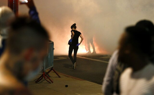 Protesters deal with tear gas in front of Phoenix Police Headquarters Saturday, May 30, in Phoenix, protesting the death of George Floyd, a handcuffed black man who died in police custody Monday with much of the arrest captured on video of a Minneapolis police officer kneeling on the neck of Floyd. (AP Photo/Ross D. Franklin)