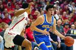 UCLA guard Jaime Jaquez Jr. (4) shields the ball from Arizona forward Ira Lee during the first half of an NCAA college basketball game Saturday, Feb. 8, 2020, in Tucson, Ariz. (AP Photo/Rick Scuteri)