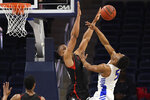 Northeastern guard Max Boursiquot blocks a shot by Hofstra guard Eli Pemberton (5) during the first half of an NCAA college basketball game for the championship of the Colonial Athletic Association men's tournament Tuesday, March 10, 2020, in Washington. (AP Photo/Nick Wass)