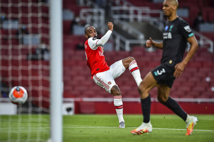 Arsenal's Alexandre Lacazette scores his team first goal during the English Premier League soccer match between Arsenal and Liverpool at the Emirates Stadium in London, England, Wednesday, July 15, 2020. (Glyn Kirk/Pool via AP)
