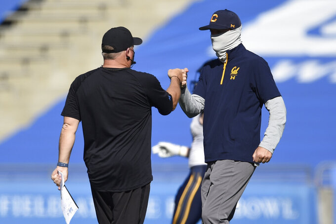 UCLA head coach Chip Kelly, left, meets with California head coach Justin Wilcox after an NCAA college football game in Los Angeles, Sunday, Nov. 15, 2020. UCLA won 34-10. (AP Photo/Kelvin Kuo)