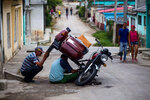In this April 1, 2018 photo, men repair a motorcycle in the Vigia neighborhood of Santa Clara, Cuba. The man who is expected to be Cuba's next president, Miguel Mario Diaz-Canel Bermudez, was born and raised in Santa Clara where he spent nine years in a role akin to a governor. (AP Photo/Desmond Boylan)