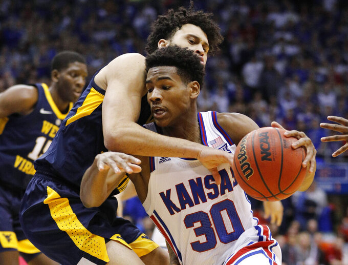 Kansas guard Ochai Agbaji (30) attempts to get past West Virginia guard Jermaine Haley (10)during the first half of an NCAA college basketball game, Saturday, Feb. 16, 2019, in Lawrence, Kan. (AP Photo/Colin E. Braley)
