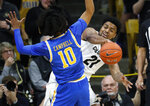 Colorado forward Evan Battey, back, passes the ball as UCLA guard Tyger Campbell defends in the first half of an NCAA college basketball game Saturday, Feb. 22, 2020, in Boulder, Colo. (AP Photo/David Zalubowski)