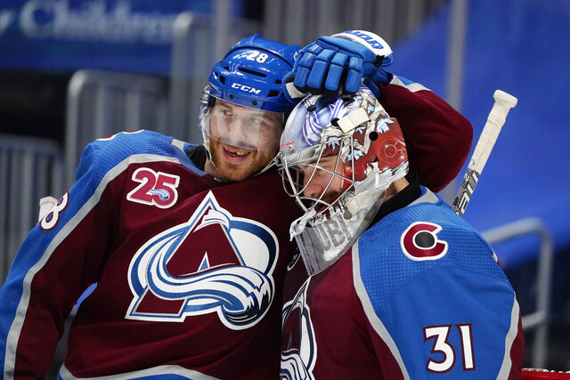 Colorado Avalanche defenseman Ian Cole, left, congratulates goaltender Philipp Grubauer after the team's NHL hockey game against the St. Louis Blues on Friday, Jan. 15, 2021, in Denver. (AP Photo/David Zalubowski)