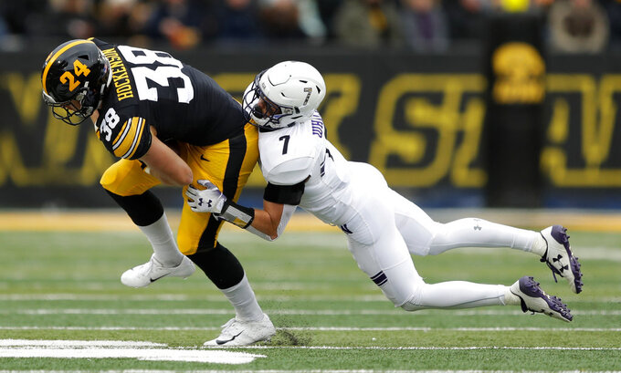 Iowa tight end T.J. Hockenson (38) is tackled by Northwestern defensive back Travis Jack Whillock (7) after making a reception during the first half of an NCAA college football game, Saturday, Nov. 10, 2018, in Iowa City, Iowa. (AP Photo/Charlie Neibergall)