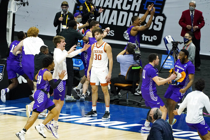 Texas' Brock Cunningham (30) stands on the court as Abilene Christian players celebrate their 53-52 upset win in a college basketball game in the first round of the NCAA tournament at Lucas Oil Stadium in Indianapolis Sunday, March 21, 2021. (AP Photo/Mark Humphrey)