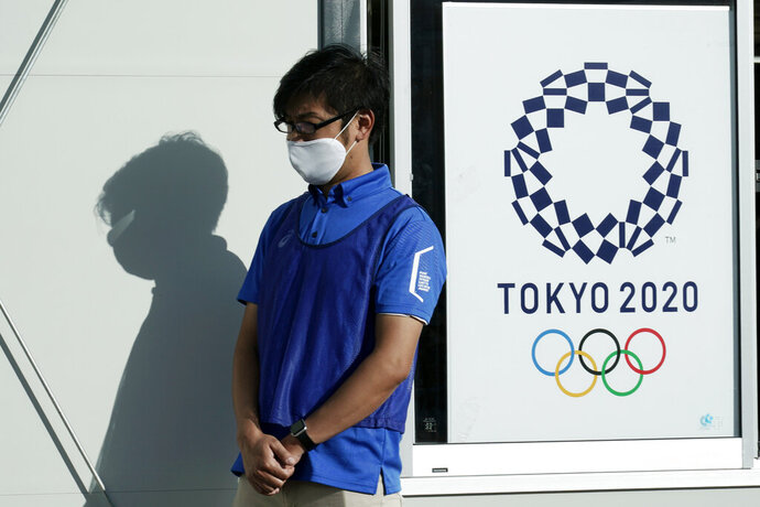A staff member participates in a screening test for spectators and officials to ensure a safe and secure Toyo Olympic Games Wednesday, Oct. 21, 2020, in Tokyo. Tokyo Olympic officials say they don't know exactly what measures will be taken against the COVID-19 pandemic at next year's Games, but they want the world to know they're working on it. (AP Photo/Eugene Hoshiko)