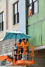 A construction crew keeps out of the sun with a sun umbrella on their boom lift as they work on an apartment building along S. Jefferson Davis Parkway in New Orleans, La. Tuesday, Aug. 13, 2019. National Weather Service issued a heat advisory for the New Orleans area Tuesday.    (Max Becherer/The Advocate via AP)