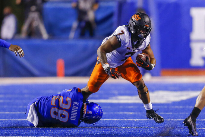 Oklahoma State running back Jaylen Warren (7) tries to pull free from Boise State cornerback Kekaula Kaniho (28) during the second half of an NCAA college football game Saturday, Sept. 18, 2021, in Boise, Idaho. (AP Photo/Steve Conner)