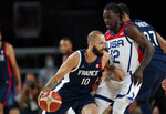 France's Evan Fournier (10) drives past United States' Jrue Holiday (12) during men's basketball gold medal game at the 2020 Summer Olympics, Saturday, Aug. 7, 2021, in Saitama, Japan. (AP Photo/Eric Gay)