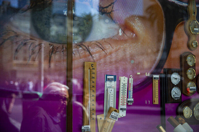 Pedestrians are reflected in the window of a store that sells glasses, watches and thermometers, and which features a large image of a person wearing glasses in its display in Santiago, Chile, Monday, Sept. 16, 2019. (AP Photo/Esteban Felix)