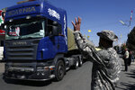 A Hezbollah fighter gestures as a convoy of tanker trucks carrying Iranian diesel crossed the border from Syria into Lebanon, arrives at the eastern town of el-Ain, Lebanon, Thursday, Sept. 16, 2021. The delivery violates U.S. sanctions imposed on Tehran after former President Donald Trump pulled America out of a nuclear deal between Iran and world powers three years ago. (AP Photo/Bilal Hussein)